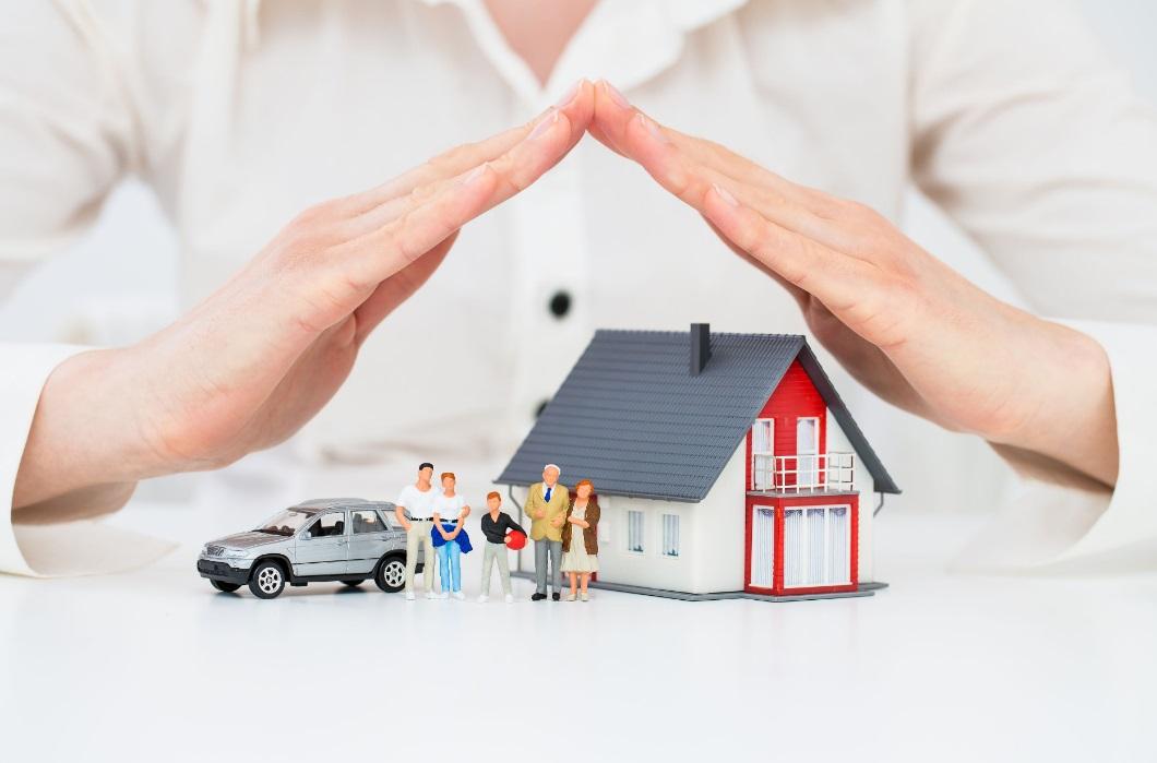 maison et personnes miniatures sous les mains